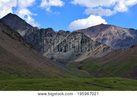 View of ravine blue sky and green meadow in Altai mountains. Altay Republic Siberia Russia.