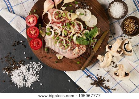 Fillet raw chicken. Fresh chicken meat on wooden board with fresh organic vegetables for cooking. Top view close-up. Rustic style. Ingredients for dietary healthy eating.