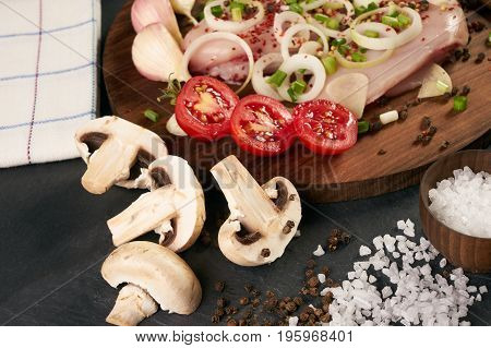 Close-up of a raw ingredients for cooking. Fresh chicken fillet ready for cook mushrooms vegetables herbs spices on a black stone background. Preparing dinner. Healthy eating low-calories diet