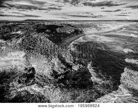 Aerial view of rugged coastline stylized in black and white with high contrast