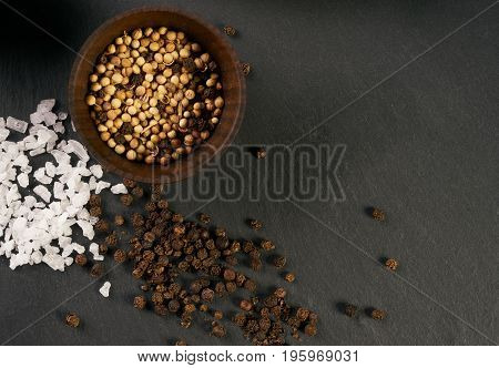 Top view of a spices and herbs on dark stone background with copy space for text. Food and cuisine ingredients.
