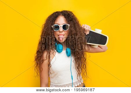 Curly haired brunette girl wearing sunglasses, headphones holding cruiser showing tongue.