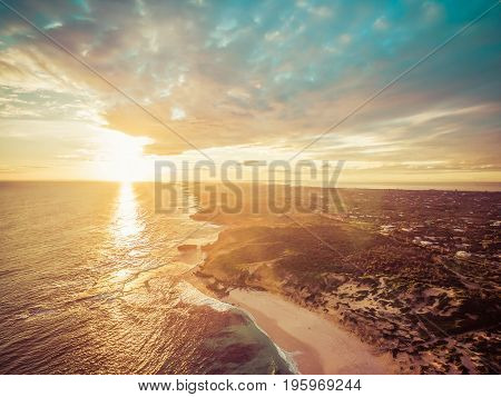 Aerial view of beautiful sunset over rugged ocean coastline