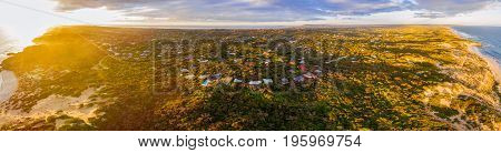 Aerial panorama of luxurious vacation homes in lush coastal vegetation at sunset. Morningon Peninsula Melbourne Australia
