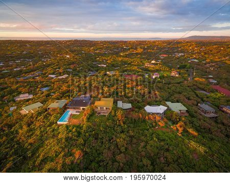 Aerial view of luxury homes among lush coastal vegetation in Rye suburb at sunset. Melbourne Australia