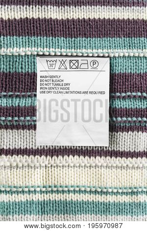 Washing instructions clothes label on wool knitted background