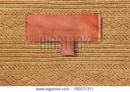 Orange blank clothes label on yellow knitted background closeup