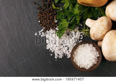 Raw fresh organic ingredients mushrooms potatoes onion and greens for cooking vegetarian soup on a dark stone background with copy space. Ingredients for prepared healthy food. Concept of sports nutrition