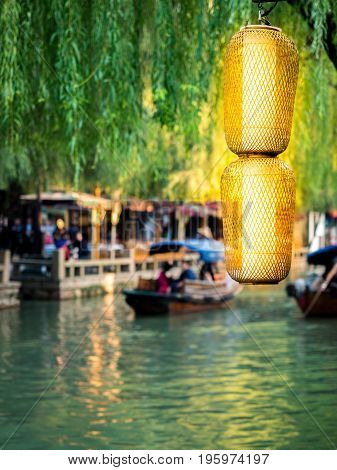 Suzhou, China - Nov 5, 2016: Brightly lit Chinese lanterns in front of waterway, boats and willows at the historic Zhouzhuang Water Town.