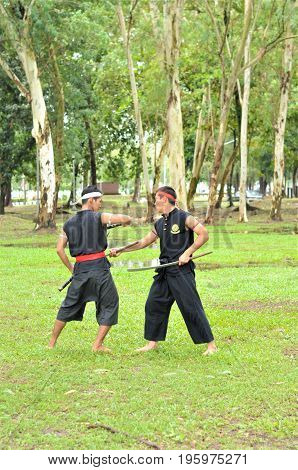 PUKED,THAILAND - AUGUST 28: Master trick of ancient fighter on August 28, 2011 in Puked Thailand.  Master show how to trick of fight with swords.
