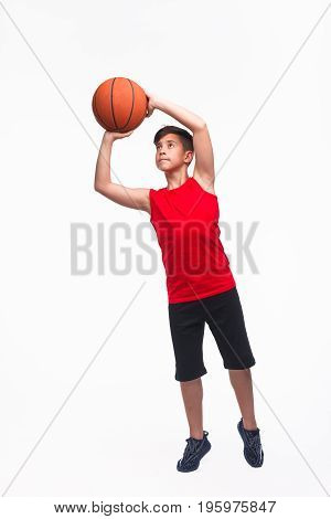 Young boy throwing a ball for game basketball isolated on white.