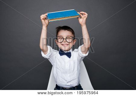 Smart boy in glasses sitting on chair and holding book above head smiling at camera.