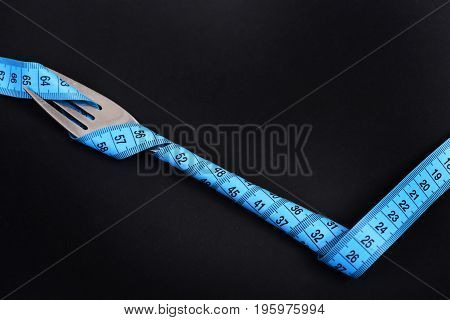 Fork Made Of Silver Metal Tied With Blue Measuring Tape