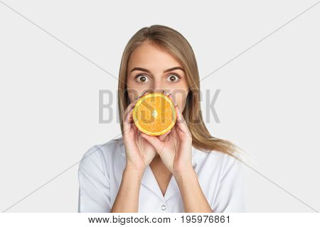 Young female doctor posing with cut orange looking at camera on white.