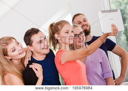 Fun bonding selfie concept. Group of diverse friends students classmates taking self photo with tablet pc computer indoors in class