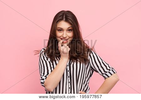 Young brunette in striped shirt looking flirty at camera on pink background.
