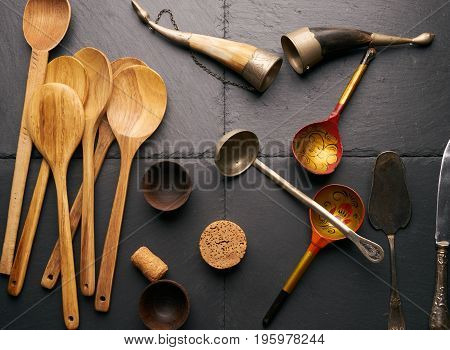 Various kitchen utensils wooden spoon round cutting board bower silver knife and spatula wooden bowls for sauce horn for wine on black stone background.