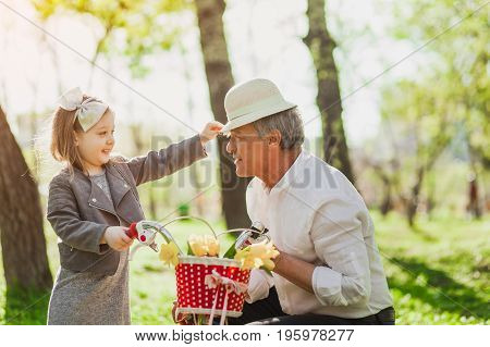 Side view of little lovely girl putting small hat on senior man while sitting bike.