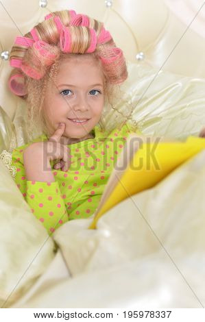 Cute little girl with pink hair curlers lying in bad and reading book