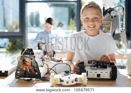 Little prodigy. Charming pre-teen boy sitting at the table full of his various robotic models, holding a robot car and smiling at the camera while his friend constructing something in the background