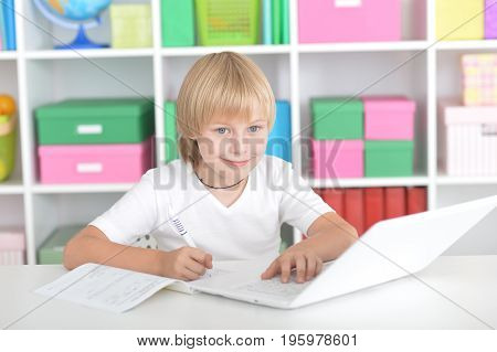 Cute little boy sitting at table with laptop while doing homework