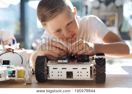 Thorough student. Lovable fair-haired boy sitting at the table and working on his own robotic vehicle while connecting the wires in it diligently