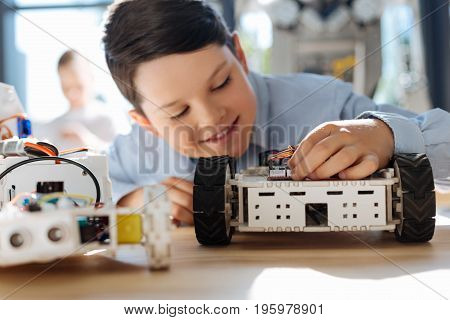 Inspiration vibes. Charming little boy sitting at the table full of robots and adjusting a small part in his robotic vehicle while looking inspired