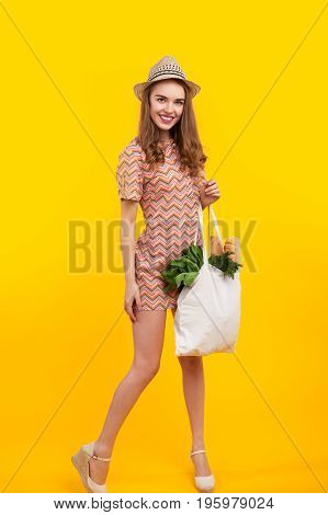 Vertical studio shot of pretty woman holding a bag with products on the yellow background.