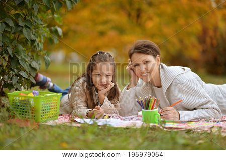 Happy mother and daughter lying on green grass in autumnal park and drawing with pencils