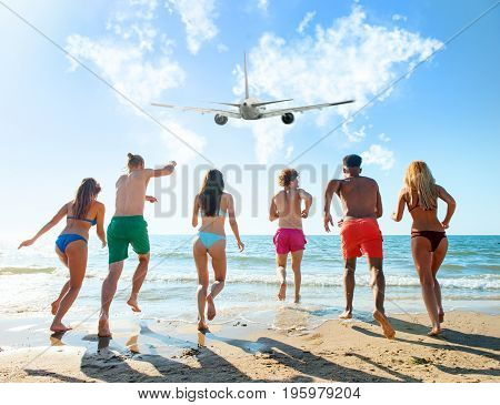 Group of friends run to the blue sea with an aircraft in the sky. Concept of travel and summer