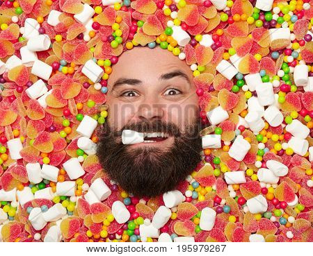 From above shot of bearded young man with marshmallow in mouth lying in candies.