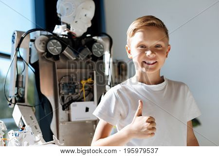 Best experience. Charming pre-teen boy posing for a photo with a big human robot and showing thumbs up, being pleased with an exhibition of robots