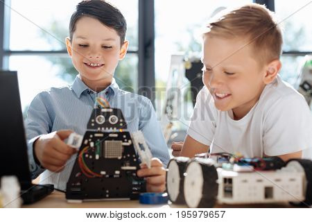 Cool toy. Pleasant pre-teen boy showing the work of his black robotic cosmic warrior to his friend looking at it with smile