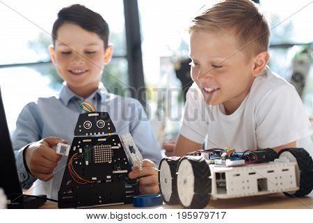 Best toy. Adorable pre-teen boy moving the arms of his robotic cosmic warrior while his fair-haired hand observing the process and smiling