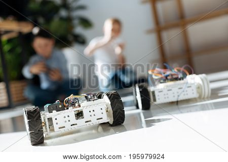 Fun pastime. The focus being on two white robotic vehicles moving across the floor, participating in a car race while their owners controlling them in the background