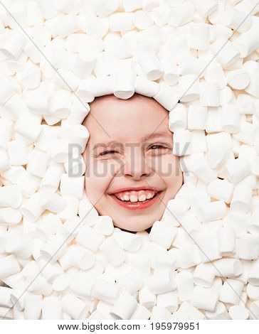 From above shot of laughing child winking at camera while lying in white marshmallows.