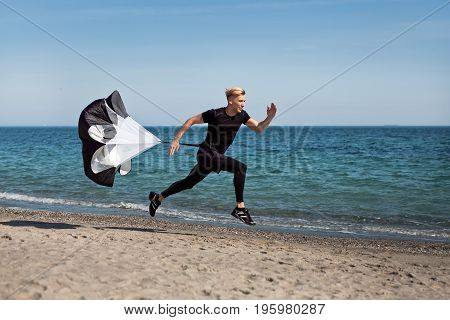 Young man dressed in black uniform running with parachute on beach on sunny day.