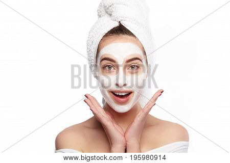 Young girl with towel on head and mask on face looking happily at camera on white background.