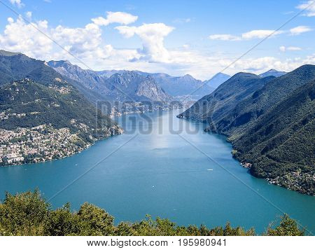 Aerial view of Lugano city with houses lake and cityscape and alpine Swiss mountains in Switzerland