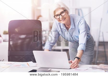 Familiar with technology. Nice practical wise executive taking her gadget for looking through some document while working at the office