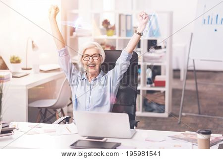 I did it. Accomplished professional business lady enjoying her success by putting her hands up after completing a project