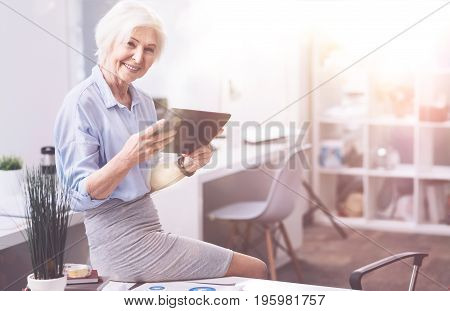 Productive hours. Prominent enthusiastic mature specialist sitting on the table and using a tablet for reading the financial report