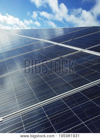 Blue solar panels producing renewable energy with sky and clouds