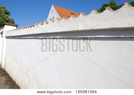 View of the old real white stone wall with roof tile surrounding house