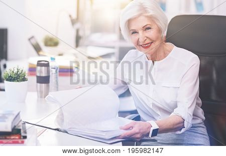 No time for retirement. Serious respected inspiring lady looking through an archive of documents while looking for a particular report