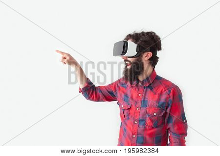 Side view of bearded man in checkered shirt and VR headset pointing away on white background.