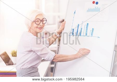 Full of ideas. Ambitious mature accomplished specialist thinking about improving the work of her company while comparing diagrams on the whiteboard