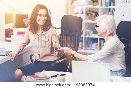 Can you help me choose. Graceful hardworking prominent businesswoman handing her colleague a list of ideas and telling her choosing a few she liking the most