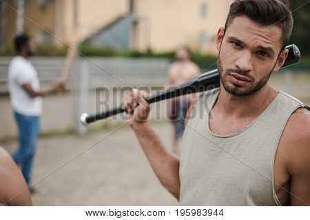 young handsome man posing with baseball bat on court