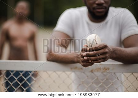 Young Handsome Man With Baseball Ball Leaning On Fence On Court